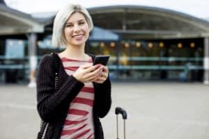 Junge Frau am Flughafen mit Handy